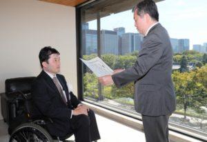 丸山社長から表彰される「視覚障害をもつ医療従事者の会(ゆいまーる)」代表の守田稔さん(左)