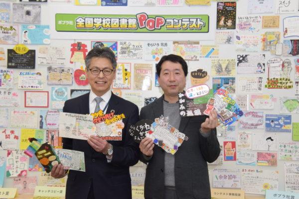 POP王賞とポプラ社賞のPOPを掲げる千葉社長と内田氏(右)