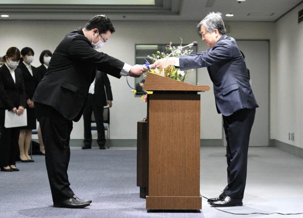毎日新聞社の丸山昌宏社長から辞令を受け取る肥沼直寛さん(左)