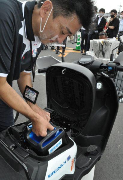 配達用のバイクにバッテリーを装着する読売新聞販売店のスタッフ(9月18日、京都市西京区で)