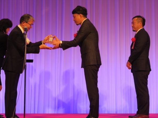 山口会長(左)から山根氏に広告大賞が贈られた
