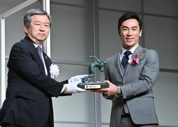 毎日新聞社の丸山昌宏社長(左)からブロンズ像を受け取るレーシングドライバーの佐藤琢磨