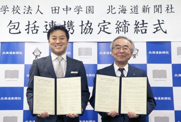 協定書を手にする田中学園理事長の田中賢介氏(左)と北海道新聞社の広瀬兼三社長