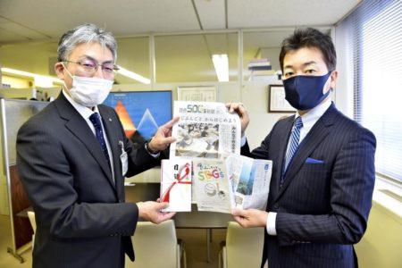 高岡市の米谷教育長(左)に読売SDGs新聞を手渡す冨田社長