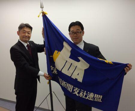 中国新聞社・北田圭一氏(左)から支社連旗を引き継ぐ古澤氏(全国地方新聞社大阪支社連盟提供)