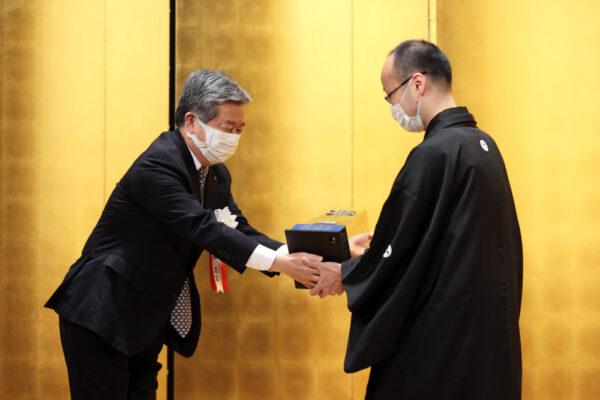 丸山社長から王将楯を手渡される渡辺王将(右)